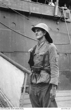A Netherlands East Indies (NEI) army soldier standing guard at the foot of the gangplank of the troop transport ship HMT Orcades, which was bringing Australian troops from the Middle East. Many of the troops were disembarked at Batavia where they became Blackforce and were taken as prisoners of war (POWs) by the Japanese.