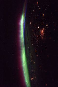 Space Station View of Auroras:    Aurora glowing on Earth's horizon with nighttime lights visible below