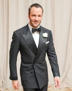 Tom Ford in a nicely cut 6x4 Tuxedo with wide peaked lapels, cloth covered buttons, satin turnback cuffs and jetted pockets