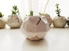 faceted white and gold ceramic vessel