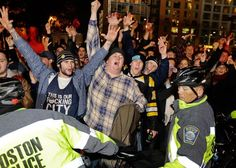 Boston Red Sox fans are ushered along a street by law enforcement officials in the street near Fenway Park following Game 6 of the World Series