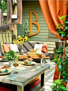 The home's exterior creates the perfect starting point for this patio's color scheme. Orange accents, such as throw pillows, hanging fabric, and oversize letter B, pop against the green exterior. Wood candle holders and potted plants bring the natural elements of the yard onto the patio. With plenty of seating and multiple tables, this patio is just right for enjoying bright summer days and warm summer nights.