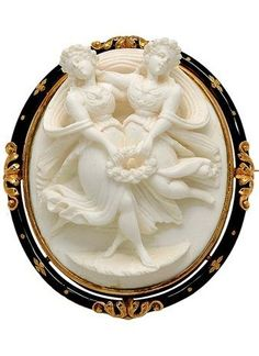 Antique Enamel and 18K Gold Lava Cameo Brooch, circa 1880. The oval black enamelled frame decorated with applied foliate motifs and centring a high relief white lava cameo depicting two nymphs with floral attributes.