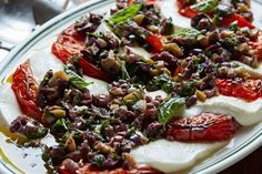 Grilled Tomatoes with Olives and Mozzarella recipe by Giada de Laurentiis. A take on a traditional caprese salad, but grilling the tomatoes helps to bring out the flavor.