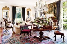 Ralph Lauren's Bedford, New York House // Living room with crystal chandelier, patterned Persian rug, and traditional furniture.
