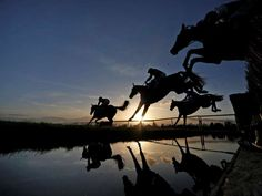 Runners clear the water jump in The Running Hare Handicap - Alan Crowhurst/Getty Images