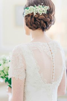 Bride wears a braided up do with fresh Lily of the Valley  | Photography by http://sarahjaneethan.co.uk/