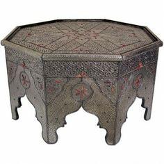 Meisterhaft und geschmackvoll wurde dieser arabische Tisch aus massivem Holz gefertigt. Aufwendig wurde eine Silberschicht -Edelmetall/ Maychort- zur Verkleidung des Holzes filigran verarbeitet. Eine dunkle Patina, die ungleichmäßig aufgetragen wird, gibt der Oberfläche den perfekten Reliefeffekt. Zusätzlich verzieren Ornamente aus präparierten Knochen und Nieten die Oberfläche.