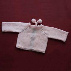 Abriguito de punto de lana con pompones, para bebé. Trasera.