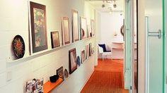 Helle Wände, eine gute Beleuchtung und verglaste Zimmertüren, die etwas Tageslicht in den Flur bringen, lassen den langen engen Raum freundlich wirken.