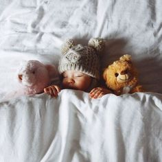 Cute little squirt snuggling with stuffed animals.