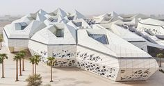 comprising five buildings, zaha hadid's KAPSARC emerges from the desert landscape as an organic, crystalline-like form defined by hexagonal honeycombs.