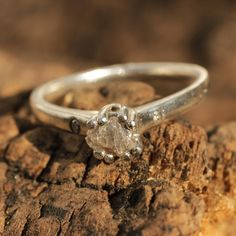 Rough diamond wedding ring in silver silver band with pave set diamonds on the side