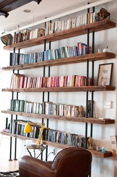 """The Tribeca Bookcase wall system is made from century-old reclaimed pine and supported by 2"""" steel pipes and will bring vintage industrial style to any living space in your home."""