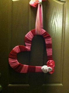 A heart cut out of cardboard, wrapped in yarn, embellishments (I made satin ribbon flowers) hung with tulle. This is a play on a few of the Valentines Day wreaths I have seen on here.