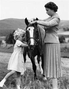 Princess Anne adjusts the bridle on her pony 'Greensleeves' with the help of her mother, Her Majesty The Queen, at Balmoral, 15 September 1955.