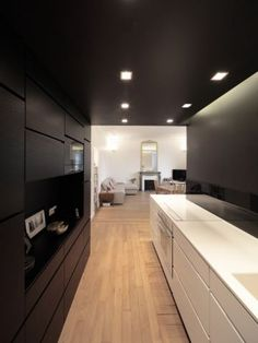cuisine dans couloir noir blanc mobilier différence hauteur sous plafond rénovation réhabilitation entrée