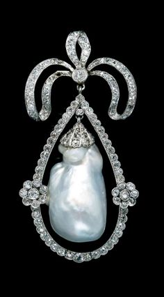 *An Edwardian Platinum, Natural Baroque Pearl and Diamond Brooch, in a bow motif, containing one natural hollow pearl measuring approximately 30.00 x 18.93 x 17.60 mm and numerous old mine and rose cut diamonds.