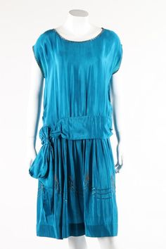 A petrol-blue 1920 crepe dress with silver beading to skirt. Front