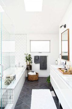 Love this large charcoal gray diagonal tiles on the floor paired with the white subway tiles and gray grout in the shower. Such a fresh look with the modern white cabinets and wood mirror!