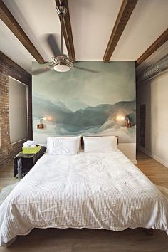 wooden beams in dark brown, on a while ceiling, in room with one brick wall, one white wall, and one smaller wall, covered in an abstract painting, in different shades of blue, large wall art