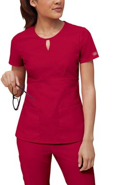 A mock wrap top features a key hold neckline, an empire waist, bust darts, patch pockets and side vents. Center back length: 25 Fabric: Cotton Poplin. Dental Uniforms, Work Uniforms, Dental Scrubs, Medical Scrubs, Scrubs Outfit, Scrubs Uniform, Stylish Scrubs, Cute Scrubs, Nursing Clothes