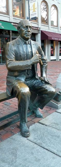 """This statue was unveiled for the 68th birthday of Boston Celtics coach and manager Arnold """"Red"""" Auerbach (1917-2006). As coach, Auerbach led the Celtics to nine NBA titles. He was also the first coach to draft an African-American player. Here, Auerbach is shown courtside, about to light a victory cigar. Visitors are invited to take a seat and join in the celebration. Also note the cast sneakers of famous athletes Bill Rodgers and Larry Bird nearby. (From http://www.publicartboston.com)"""