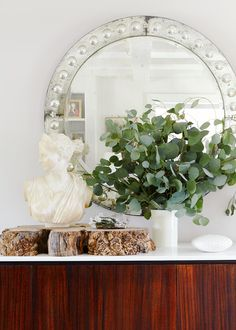 Round antique mirror and bust with small plant