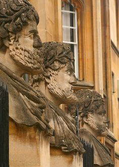 Oxford Heads  Three of a series of stone heads looking out from atop railings at Oxford close to the Sheldonian Theatre and the Museum of Science. They seem to be of Roman emperors.