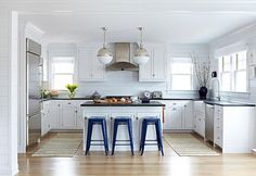 U shaped blue and white beach bungalow kitchen boasts two Hicks Pendants hung over a white kitchen island topped with black marble countertops seating three navy blue tolix stools sat on rift sawn oak floors.