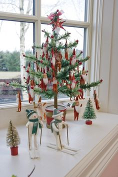 Vintage feather tree with a collection of small chenille Santas, with clay faces, decorating it.