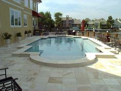 Geometric pool with travertine coping and patios