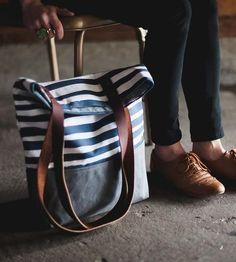 Bolsa de tecido ou lona com alças de couro.