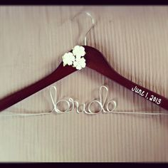 Gifts for bridesmaids - this idea inspired me to have the vendor make each bridesmaid a hanger with her first name.  Bridal Hanger with 3 flowers & date. via Etsy.