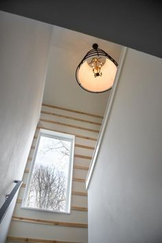 A dimmer switch allows the industrial pendant light to give way to ample natural light that floods through a large window into the stairwell.