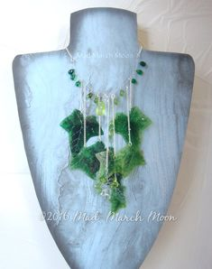 Ivy Cascade Necklace, handmade acetate leaves with hand piped veining, czech glass beads and silver plated chains.  perfect for your elven or nature centric look, bathe yourself of lush greens and subtle sparkle.  Each leaf is hand produced, with piped transparent veining. The leaves are rich transparent colour and have the qualities of glass. Teamed with Czech glass beads in tones of green and crystal clear this necklace is hand strung with an organic style. The silver plated chain and…