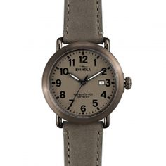 The Shinola Runwell 41mm gray leather watch with gray dial and date indicator features a stainless steel case along with a Swiss quality quartz Argonite 705 movement, which is hand-assembled in Detroit from nearly four-dozen Swiss made parts.
