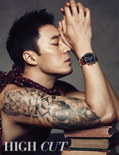 So Ji Sub bares his tattooed biceps and broods in the arms of a girl in the latest volume of High Cut.