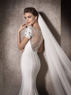 MARCELA is a sublime wedding dress with a gorgeous tulle back embellished with gemstone embroidery. Designed in crepe, it has a discreet round neck