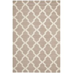 Grace your bedroom or living room with this beige wool rug. This hand-tufted rug features a distinctive high-low construction and Moroccan inspired detailing. Equipped with a durable cotton canvas backing, this piece is both stylish and durable.
