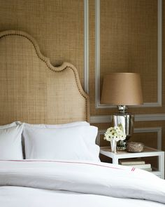 sand grasscloth wallpaper, burlap headboard with French brass tacks, mercury glass lamp with linen shade, crisp white hotel bedding with red stitching and white open nightstand