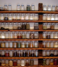spice wall (made from reclaimed wood) - uniformity of space and rows of glass jars filled with fragrant spices