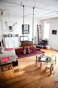 sala branca e moderna, com pé direito alto, tem chão de madeira e trapézio