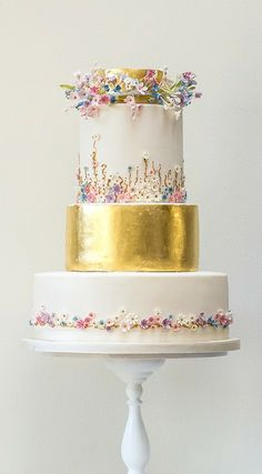 This cake is FABULOUS! This whimsical cake design, created by Rosalind Miller Cakes, features two tiers covered in edible gold leaf, as well as tiny sugar wildflowers that look as if they were handpicked and fashioned into romantic flower crowns. Metallic Wedding Cakes, Luxury Wedding Cake, Beautiful Wedding Cakes, Gorgeous Cakes, Pretty Cakes, Cute Cakes, Amazing Cakes, Gold Wedding, Floral Wedding