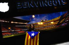 A woman holds a Pro-Independence Catalan flag as she poses for a picture in front of a picture of the Camp Nou stadium ahead of the UEFA Champions League Group E match between FC Barcelona and FC BATE Borisov at the Camp Nou on November 4, 2015 in Barcelona, Catalonia.