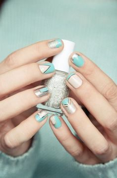 A pretty looking nail art design in bold shapes using baby blue and white polish with thin strips of silver metallic foil separating the shapes.