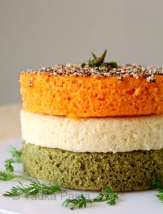 Tricolor Dhokla Tiranga Suji Dhokla 1.5 cups sour curds salt to taste-about 1.5 tsps 1.5 cups fine semolina/suji/rawa 2 carrots, chopped and boiled 1Tomato, chopped A dash of chilli powder 2tbs grated coconut 1tsp ginger paste 1/2 cup prepared coriander/mint green chutney or paste 1.5 tsps Eno brand fruit salt For the tadka- 2tbs sesame oil A pinch of asafoetida/hing 1tsp mustard seeds 2tsps sesame seeds -2 Green chillies, slices, optional A pinch of red chilli powder or paprika