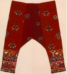 Woman's trousers, Indian; early 1900s.  Materials: silk, embroidered with silk, mirrors.  The delicate floral patterns are typical of fine embroideries from the Kutch district in Gujarat. Shiny mirror discs of various sizes and shapes are intricately attached to the garment and trousers using minute stitches.