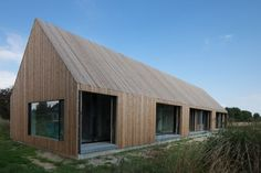 CAAN Architect's House VS - vertical timber cladding used to wall and roof with punched windows.