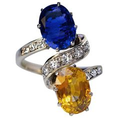 Circa 1950 A vintage French platinum and white gold ring features royal blue and tangerine orange oval sapphires accented by a diamond-set stylized ribbon. The blue sapphire measures 10 x x mm, approximately ct; the orange sapphire is 10 x x mm, The Sapphires, Orange Sapphire, Sapphire Diamond, Blue Orange, Yellow, Sterling Silver Jewelry, Antique Jewelry, Vintage Jewelry, Engraved Jewelry
